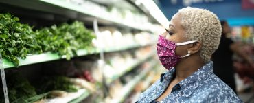 Woman with a cloth face mask shopping at a grocery store