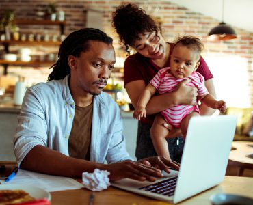 A father and mother with their baby at a laptop.