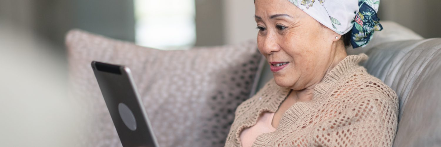 A senior woman with cancer using a tablet at home.